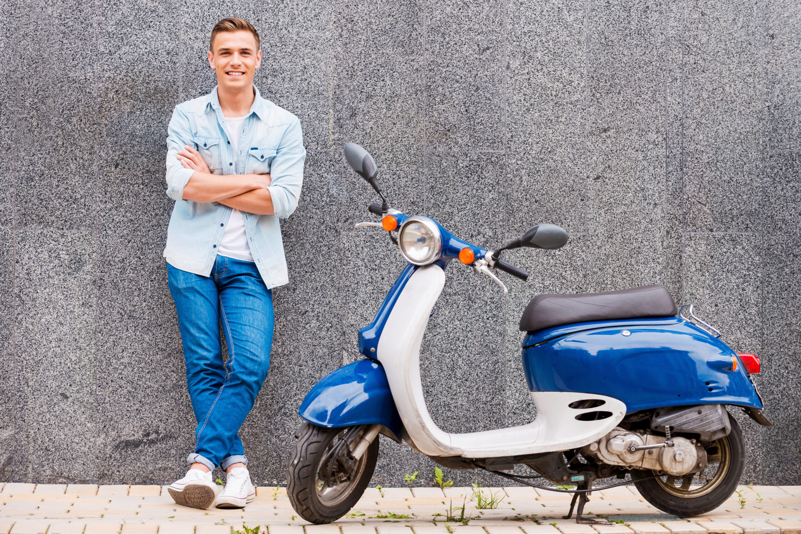 Me and my new scooter. Handsome young man leaning at the wall and smiling while standing near his new scooter
