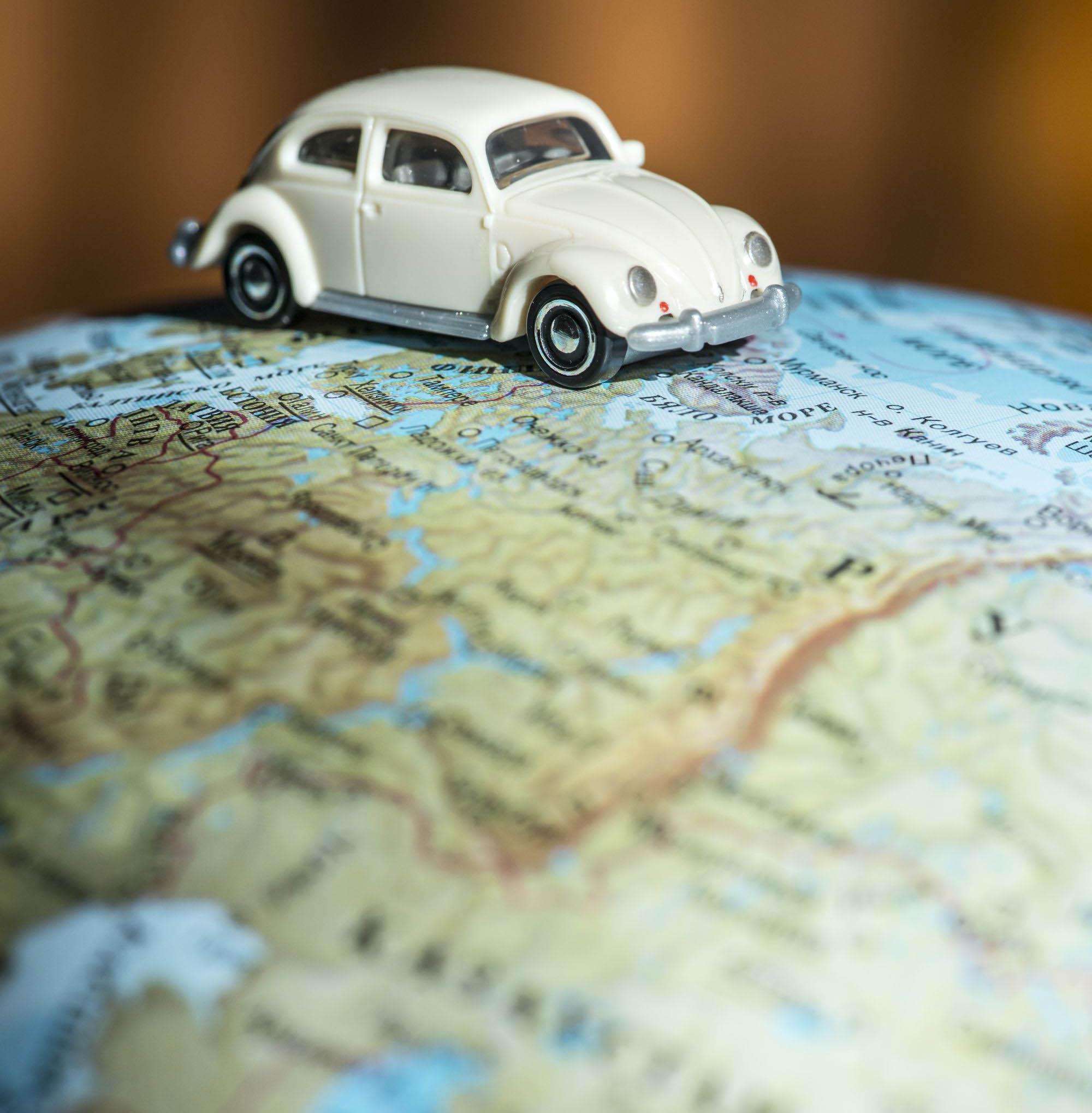Car figure on globe. Miniature car toy